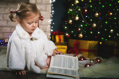 Baby girl reading book with fairy tale at Christmas Stock Photo