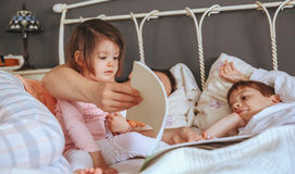 Baby girl reading book with family in the bed Stock Photography