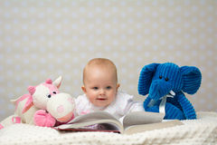Baby girl reading a book. Happy baby girl reading a book with little friends Stock Photos