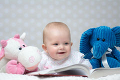 Baby girl reading a book. Happy baby girl reading a book with little toy friends Royalty Free Stock Images