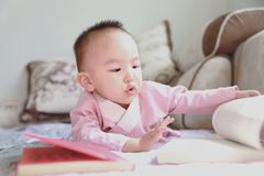 Baby girl reading book Lie down on sofa royalty free stock image