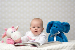 Baby girl reading a book. With little friends Stock Photos