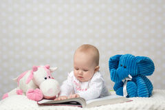 Baby girl reading a book. With little toy friends Royalty Free Stock Photos