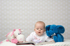 Baby girl reading a book. With little toy friends Stock Image