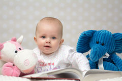 Baby girl reading a book. With little toy friends and lookin at the camera Stock Photos