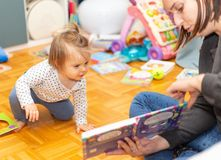 Baby. Girl. Reading. Book. Mother. Joy. Cute stock photography