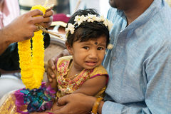 Baby girl received flower garland from priest. Royalty Free Stock Photo