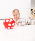 Baby girl with red ball. Baby girl amazed by red ball Royalty Free Stock Image