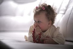 Baby girl with red beads in profile Stock Images