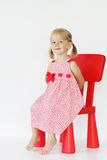 Baby girl on red chair. Cute baby girl in red dress on chair stock photography