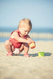 Baby girl in red dress playing on sandy beach near the sea. Royalty Free Stock Photo