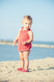 Baby girl in red dress playing on sandy beach near the sea. Stock Image