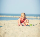 Baby girl in red dress playing on sandy beach near the sea. Royalty Free Stock Photography