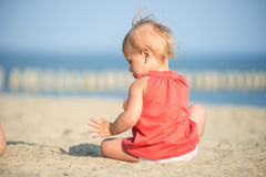 Baby girl in red dress playing on sandy beach near the sea. Stock Photography