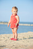 Baby girl in red dress playing on sandy beach near the sea. Royalty Free Stock Images