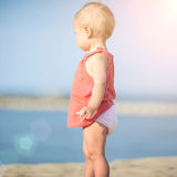 Baby girl in red dress playing on sandy beach near the sea. Stock Photo