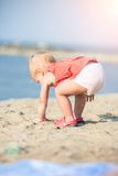Baby girl in red dress playing on sandy beach near the sea. Stock Photos