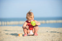 Baby girl in red dress playing on sandy beach near the sea. Stock Images