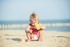 Baby girl in red dress playing on sandy beach near the sea. Royalty Free Stock Image