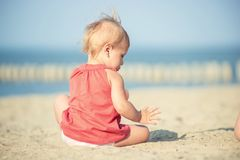 Baby girl in red dress playing on sandy beach near the sea. Royalty Free Stock Photos