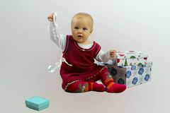 Baby Girl In Red Dress Sitting And Opening Gift Boxes. Stock Image