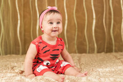 Baby girl in red with funny face stock image