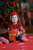 Baby girl with red gift near Christmas tree Stock Photos