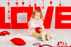 Baby girl with a red heart candy Stock Photography