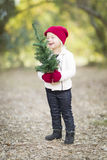 Baby Girl In Red Mittens and Cap Holding Small Christmas Tree Royalty Free Stock Image