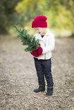 Baby Girl In Red Mittens and Cap Holding Small Christmas Tree Royalty Free Stock Images