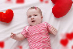 Baby girl with red plush hearts lying Royalty Free Stock Photos
