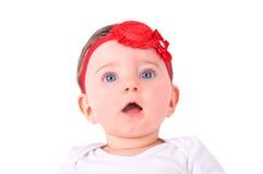Baby girl with red ribbon. Baby girl with red ribbon on white sofa Stock Photos