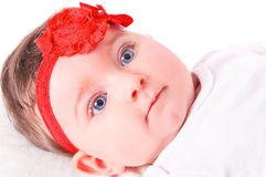 Baby girl with red ribbon. Royalty Free Stock Images