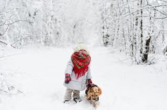 Baby girl in red scarf with small dog in a winter forest. Horizontal portrait Royalty Free Stock Image