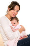 Baby girl relaxed with pacifier hug in mother arms. On white background stock photo