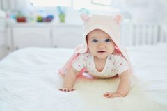 Baby girl relaxing in bedroom in pink clothes or towel with ears. Adorable seven months baby girl relaxing in bedroom in pink clothes or towel with ears stock photography