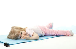 Baby girl relaxing after sport on a training mat Royalty Free Stock Image