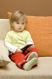 Baby girl with remote control. On  sofa Stock Photo