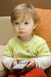 Baby girl with remote control. On  sofa Stock Photography