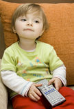 Baby girl with remote control. Sweet baby girl with remote control on sofa Royalty Free Stock Images