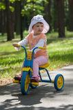Baby girl rides tricycle Stock Photo