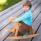 Baby girl riding small wooden horse toy Royalty Free Stock Image