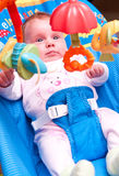 Baby girl on rocker. Cute baby girl on a rocker, looking at hanging toys royalty free stock photography
