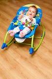 Baby girl in rocker. Cute baby girl in rocker on laminate floor royalty free stock images