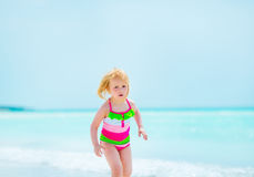 Baby girl running on beach Stock Photography