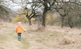 Baby-girl running in the garden Stock Image