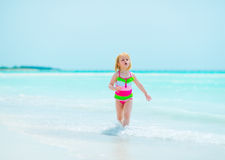 Baby girl running on sea shore Royalty Free Stock Photo