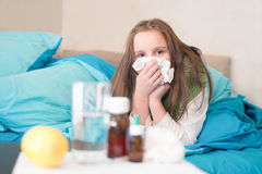 The baby girl with a runny nose. Girl child with a cold holding handkerchief Royalty Free Stock Image