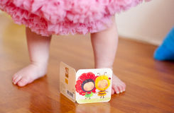 Baby girl's feet, greeting card and fluffy skirt. Baby girl's feet, greeting card and pink fluffy skirt Royalty Free Stock Image