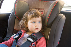 The  baby girl safely sitting in his car seat Royalty Free Stock Photos
